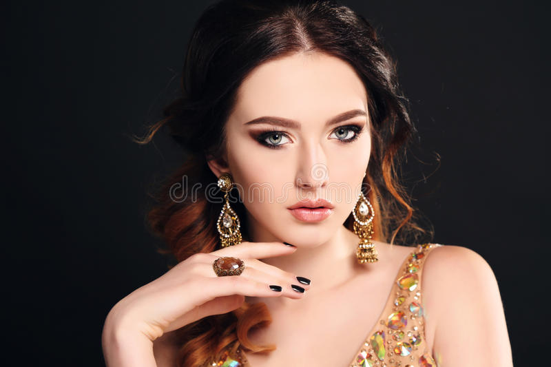 Woman with dark hair wearing luxurious sequin dress and bijou. Fashion studio photo of beautiful sensual woman with dark hair wearing luxurious sequin dress and stock image