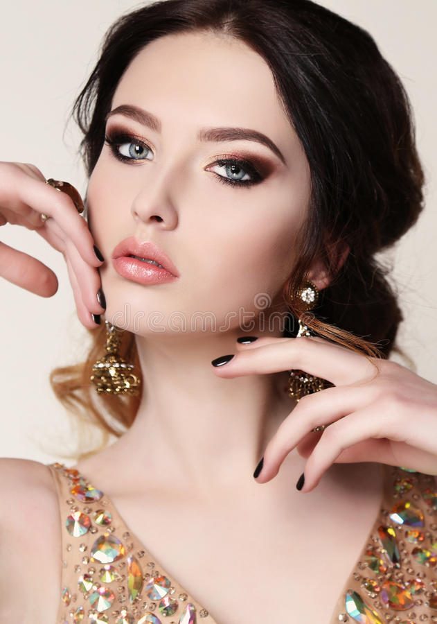 Woman with dark hair wearing luxurious sequin dress and bijou. Fashion studio photo of beautiful sensual woman with dark hair wearing luxurious sequin dress and stock images