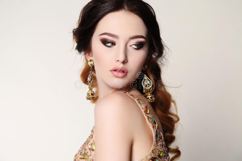 Woman with dark hair wearing luxurious sequin dress and bijou. Fashion studio photo of beautiful sensual woman with dark hair wearing luxurious sequin dress and royalty free stock images