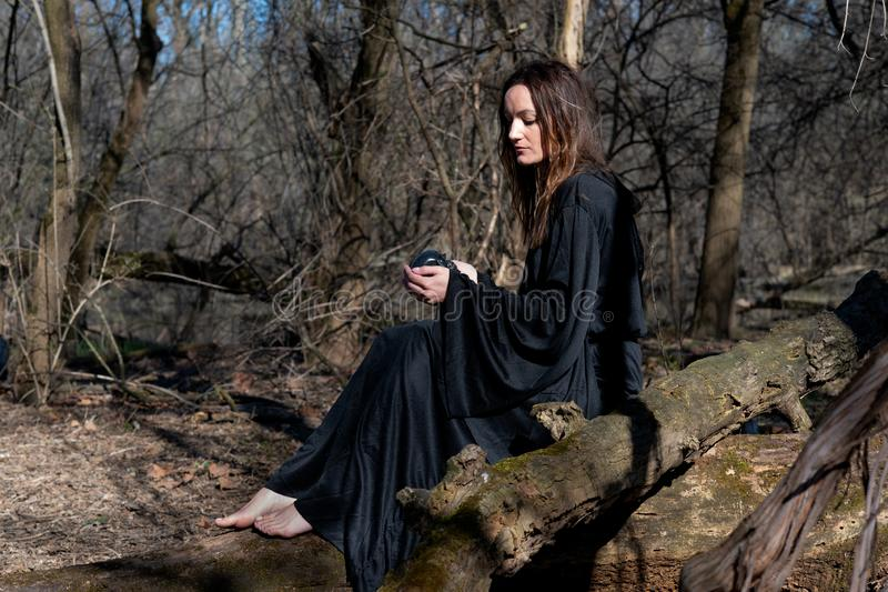 Woman with dark long hair in black robes sitting on a tree trunk in the forest. Back to Nature concept. Witchcraft and magic royalty free stock images