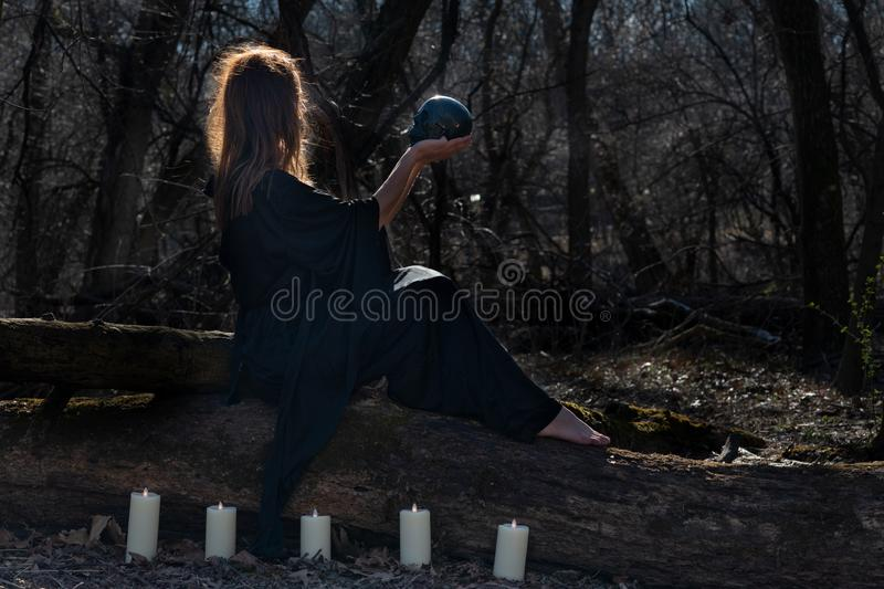 Woman with dark long hair in black robes surrounded by white burning candles sitting on a tree trunk in the forest. Back to Nature royalty free stock photography