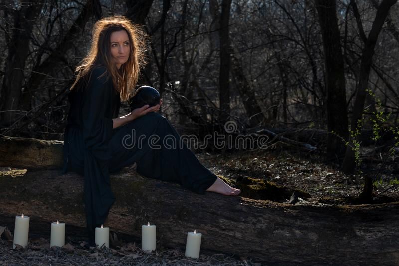 Woman with dark long hair in black robes surrounded by white burning candles sitting on a tree trunk in the forest. Back to Nature royalty free stock photos