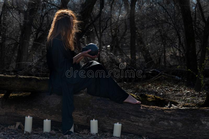 Woman with dark long hair in black robes surrounded by white burning candles sitting on a tree trunk in the forest. Back to Nature stock photos