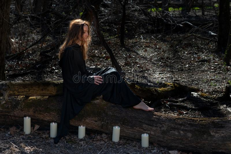 Woman with dark long hair in black robes surrounded by white burning candles sitting on a tree trunk in the forest. stock images