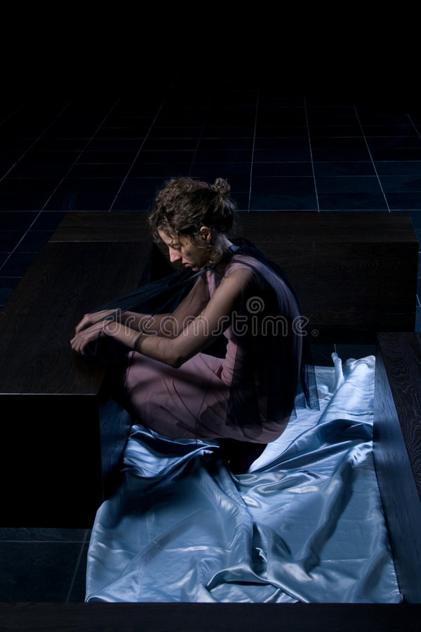 Woman in a dark room stock images