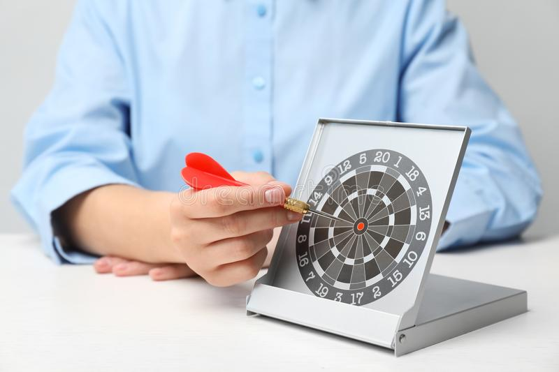 Woman with darts at table. Business trainer concept royalty free stock photos