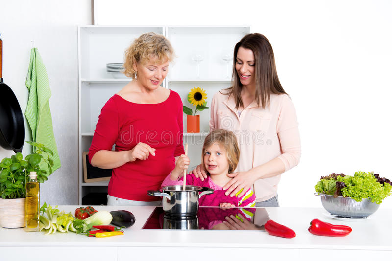 Woman with daughter and grandchild together in the kitchen royalty free stock image