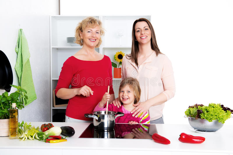 Woman with daughter and grandchild together in the kitchen royalty free stock images