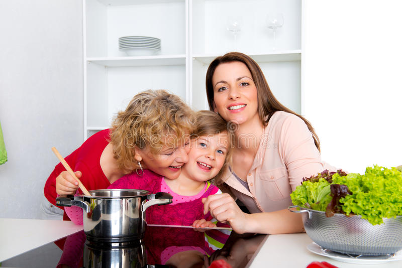 Woman with daughter and grandchild together in the kitchen royalty free stock photography