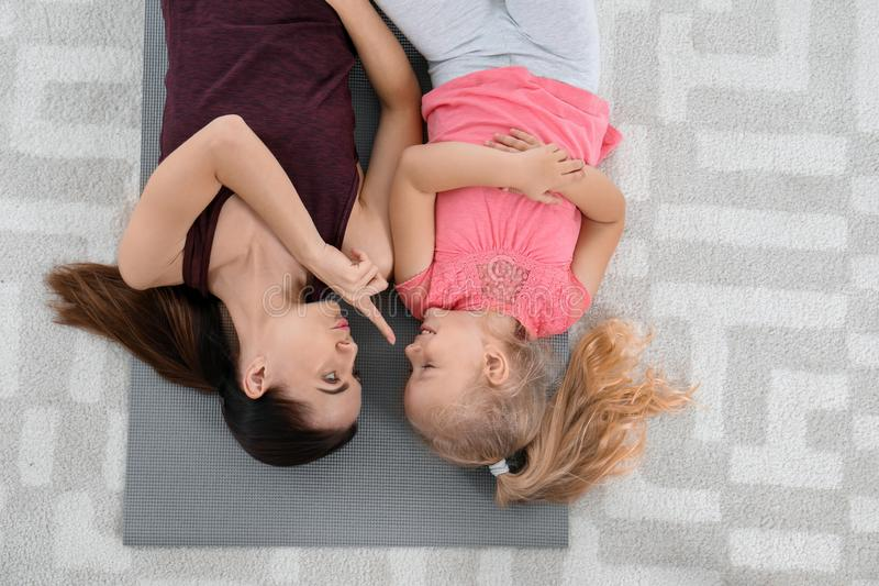 Woman with daughter lying on fitness mat at home stock image