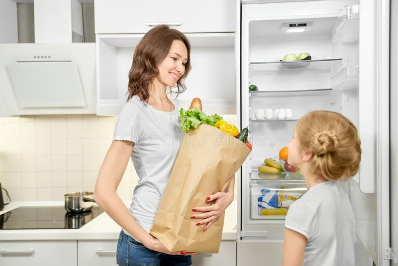 Woman and daughter with products bag near empty fridge. stock images