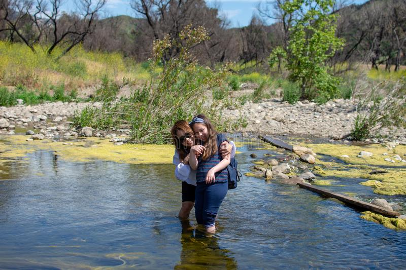 Woman and daughter standing and laughing tother while playing in a stream or river stock photos