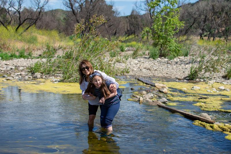 Woman and daughter standing and laughing tother while playing in a stream or river royalty free stock photography
