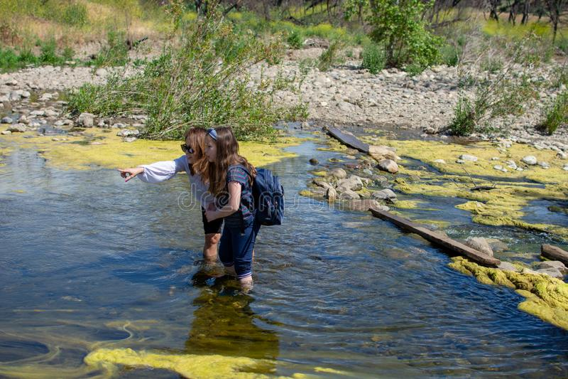 Woman and daughter standing and pointing water while standing in a stream or river royalty free stock images