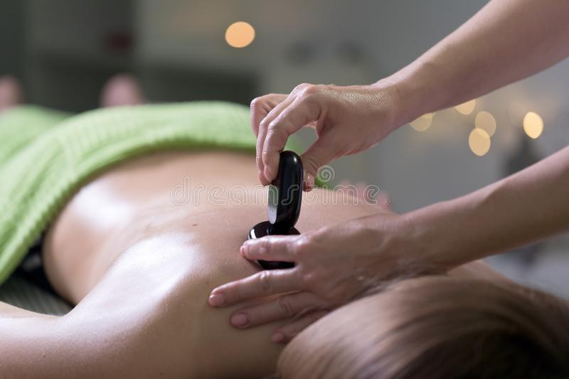 Woman in a day spa getting a stone treatment stock images