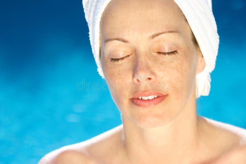 Woman at dayspa. Woman wearing towel at poolside