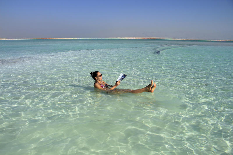 Woman in Dead sea lies in the water stock photos