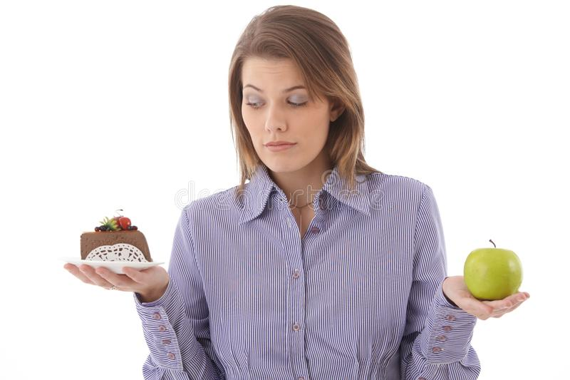 Woman debating cake or apple. Young woman debating between cake or apple, sugar or fruit, dessert or healthy food royalty free stock photos