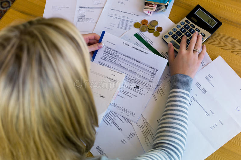 Woman with debts and bills royalty free stock image