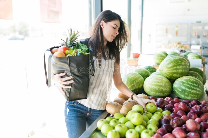 Woman Decided To Buy Green Apples Also While Shopping In Store. Female buyer holding grocery bag while choosing juicy green apples at organic market stock photo