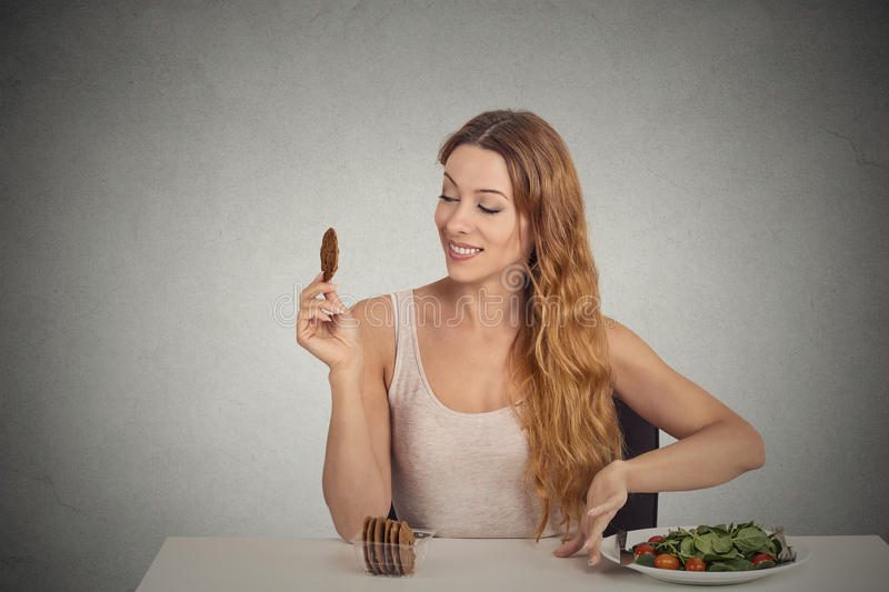Woman decided to eat sweet cookie not healthy food. Happy young woman decided to eat sweet cookie not healthy food green salad on grey wall background. Human stock photos
