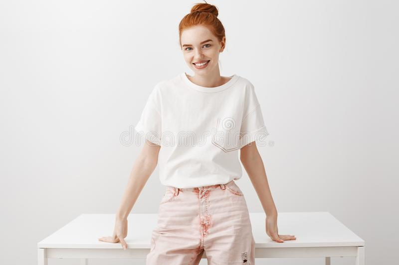 Woman decided to sit and talk honestly. Friendly good-looking feminine ginger girl with bun hairstyle, sitting on table. And smiling joyfully at camera, leading stock photography