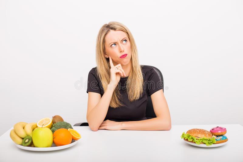 Woman deciding between healthy and unhealthy foods stock images