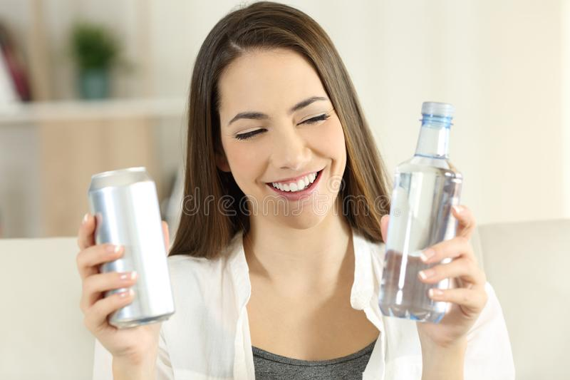 Woman deciding between water or soda refreshment. Front view portrait of a happy woman deciding between water or soda refreshment sitting on a couch in the royalty free stock photo