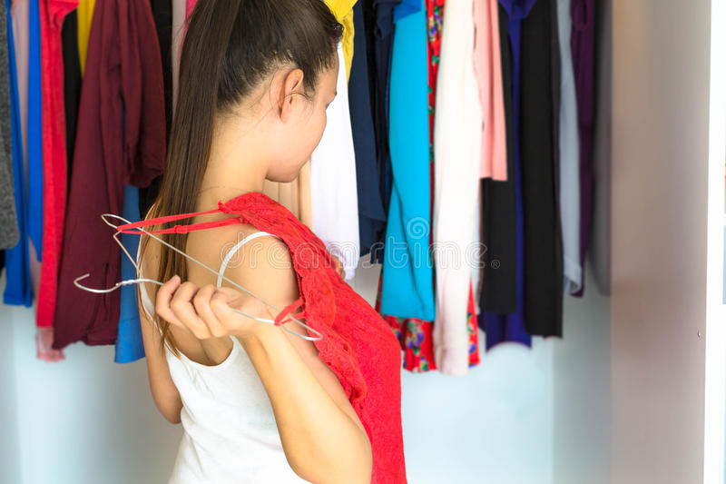 Woman deciding on what to wear in front of her closet stock photography