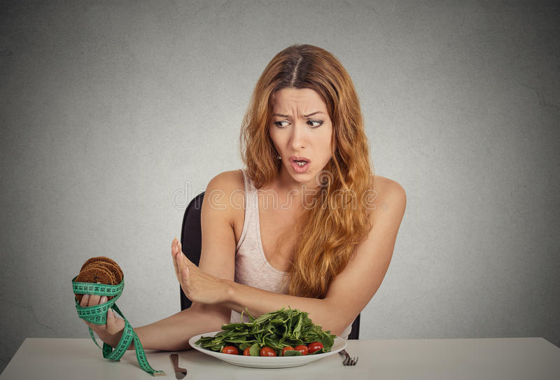 Woman deciding whether to eat healthy food or sweet cookies she craving stock image