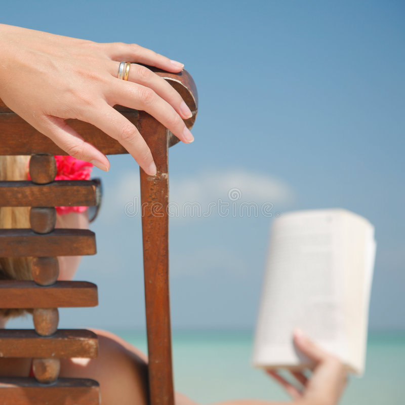 Woman in deckchair Reading. Woman reading in deckchair on tropical beach stock photo