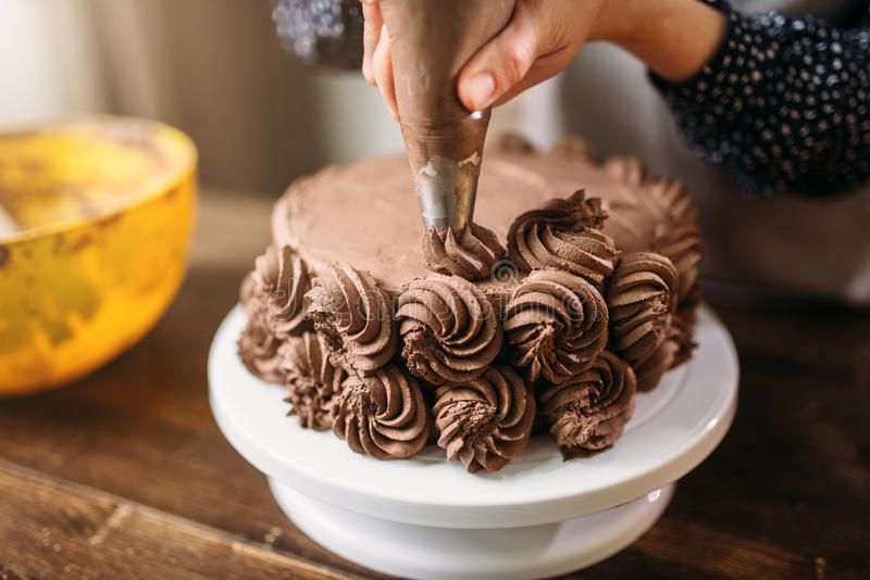 Woman decorate cake with culinary syringe royalty free stock photography