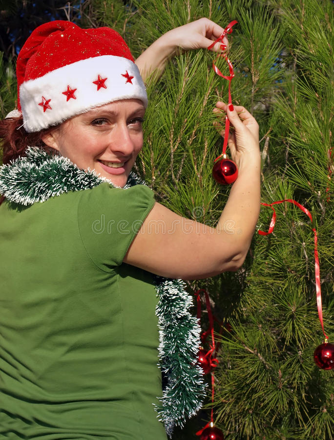 Woman decorating Christmas tree royalty free stock photo