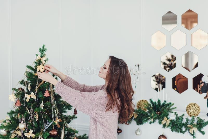 Woman decorating the christmas tree royalty free stock photography