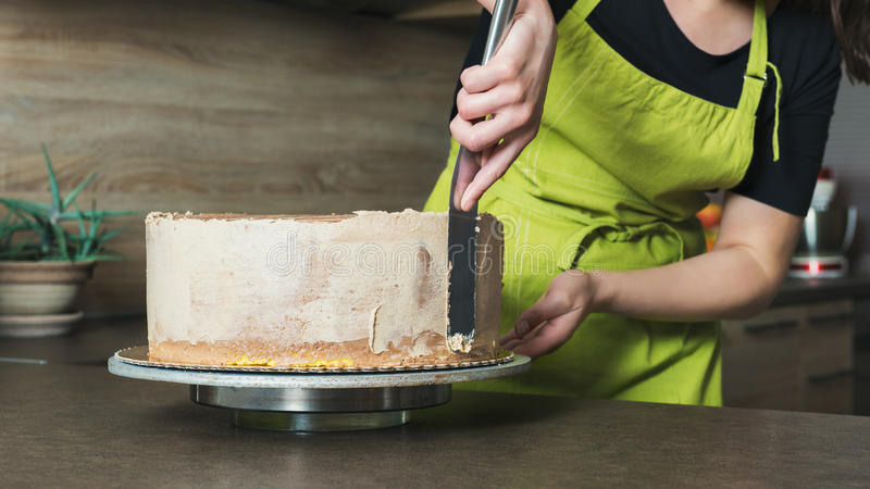 woman decorating a delicious layered sponge cake with chocolate icing cream stock photos