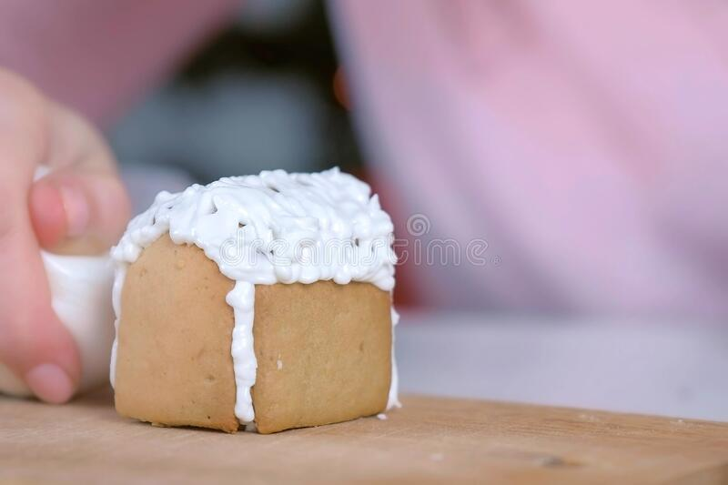Woman is decorating gingerbread house with sugar sweet icing, hands closeup. royalty free stock photography