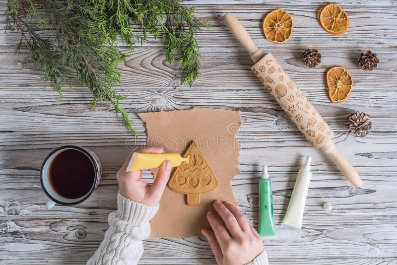 Woman decorating honey gingerbread cookies in a form of christmas tree on wooden grey table and craft paper. Blank biscuit gingerbread small fir, ready to stock photography
