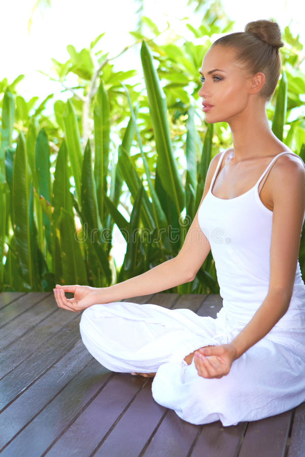 Woman in deep contemplation while meditating. Woman sitting in the lotus position on a wooden deck surrounded by tropical plants in deep contemplation while stock photos