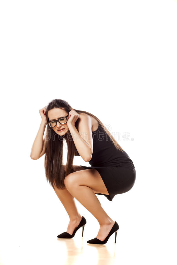 Woman in defensive position. Scared woman crouched with hands in defensive position stock image