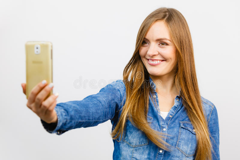 Woman in denim shirt taking self picture with phone. Technology internet and happiness concept. Young fashion woman in denim shirt taking self picture selfie stock image