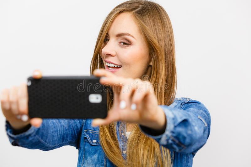 Woman in denim shirt taking self picture with phone. Technology internet and happiness concept. Young fashion woman in denim shirt taking self picture selfie royalty free stock photo