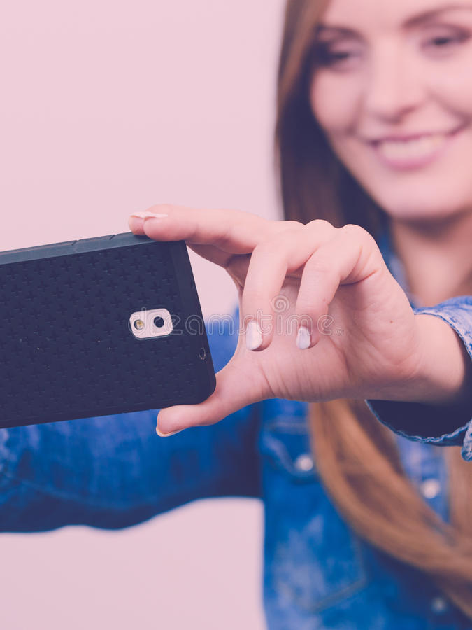 Woman in denim shirt taking self picture with phone. Technology internet and happiness concept. Young fashion woman in denim shirt taking self picture selfie royalty free stock photos