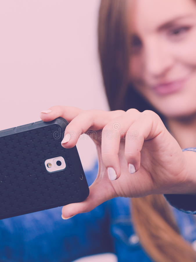 Woman in denim shirt taking self picture with phone. Technology internet and happiness concept. Young fashion woman in denim shirt taking self picture selfie royalty free stock image