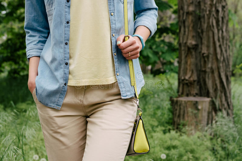 Woman in denim shirt and a yellow T-shirt and pants walking on the green park. In spring royalty free stock photos