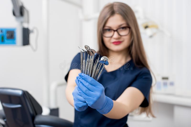 Portrait of female attractive dentist holding dental tools - at the modern dental office stock image