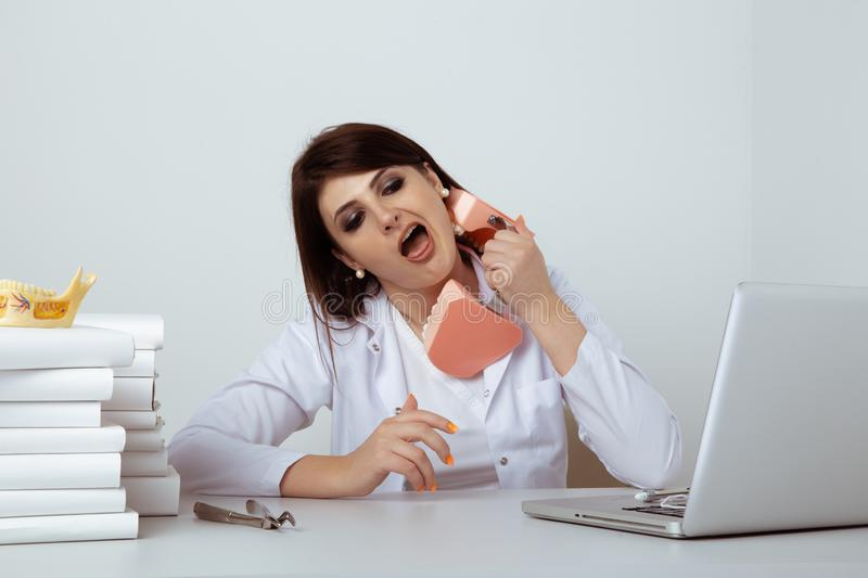 Woman dentist in office having fun and playing model jaw. stock images