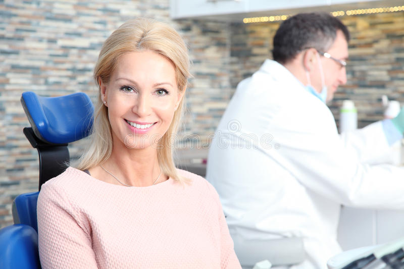 Woman at the dentist. Portrait of beautiful middle age women sitting at dentistry while male dentist working at background stock photo