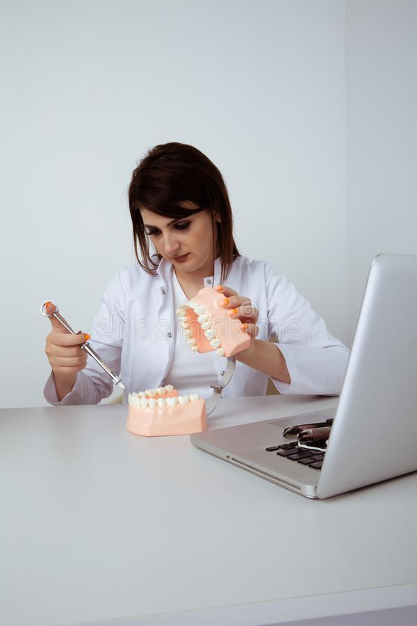 Woman dentist sitting at the table in office with dental staff isolated. stock photo
