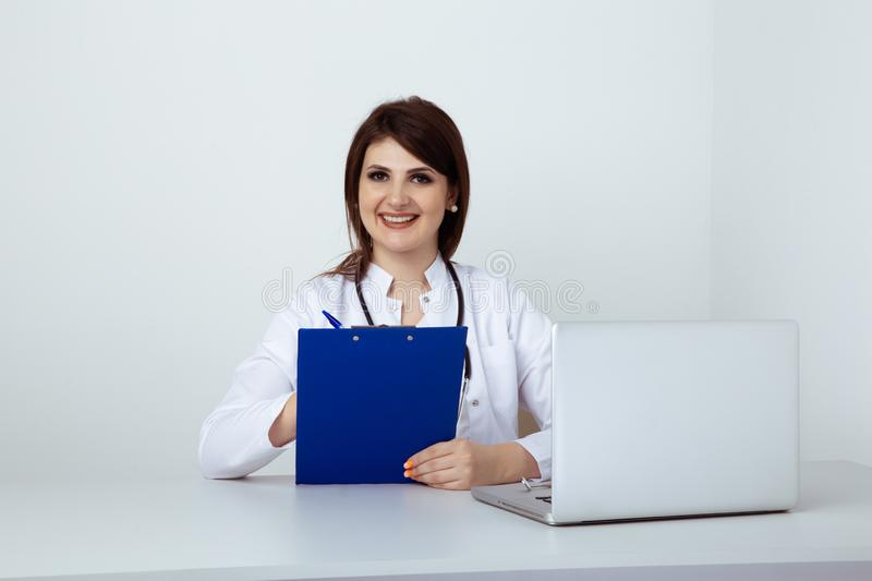 Woman dentist sitting at the table in office with dental staff isolated. royalty free stock images