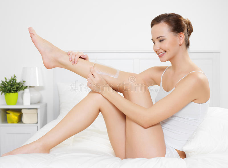 Woman depilating skin on legs by waxing stock photo
